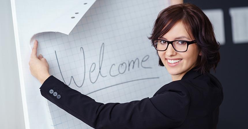 """Eine Mitarbeiterin schreibt """"Welcome"""" auf das Flipchart."""